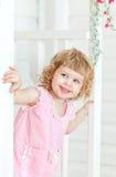 Kleines nettes Mädchen untersucht die Straße und das Lächeln von hinten Tür Lizenzfreie Stockfotos
