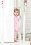 Kleines nettes Mädchen untersucht die Straße und das Lächeln von hinten Tür Stockfotografie