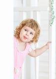 Kleines nettes Mädchen untersucht die Straße und das Lächeln von hinten Tür Stockbild
