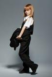 Kleines nettes Mädchen in voller Länge im weißen Hemd, in der schwarzen Weste, in der schwarzen Hose, lokalisiert über Grau Lizenzfreies Stockbild