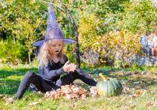 Kleines nettes Mädchen wirft einen Bann auf Halloween herein Stockfotos