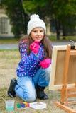 Kleines nettes Mädchen zeichnet Farben auf einem Gestell draußen Lizenzfreie Stockfotografie