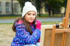 Kleines nettes Mädchen zeichnet Farben auf einem Gestell draußen Stockfoto