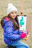 Kleines nettes Mädchen zeichnet Farben auf einem Gestell draußen Lizenzfreies Stockbild