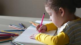 Kleines nettes kleines Mädchen zeichnet ihr Haus mit farbigen Bleistiften 4K stock video