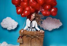Kleines nettes Mädchenfliegen auf rotem Herzen steigt Valentinsgrußtag im Ballon auf Stockfotografie