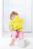 Kleines nettes Mädchen im rosa Kleid, das auf weißem rustikalem Portal sitzt und versteckt ihr Gesicht hinter Blumenstrauß von ge Stockfotografie