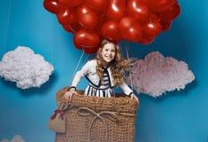 Kleines nettes Mädchenfliegen auf rotem Herzen steigt Valentinsgrußtag im Ballon auf Lizenzfreies Stockfoto