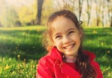 Kleines nettes Schulmädchen, das Spaß bei Sonnenuntergang hat Stockfotos