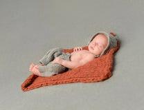 Kleines neugeborenes Baby, das auf gestrickter Decke schläft Lizenzfreie Stockfotografie