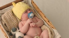 Kleines neugeborenes Baby in einem gelben Hut schläft und säugt Attrappe stock footage