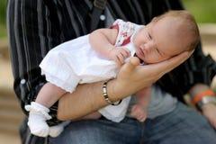 Kleines neugeborenes Schätzchen in den Händen des Vaters Stockfotografie
