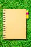 Kleines Notizbuch auf Feld des grünen Grases Stockfotos