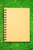 Kleines Notizbuch auf Feld des grünen Grases Stockfoto