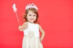Kleines Prinzessinmädchen, das ihren magischen Stab in Richtung zur Kamera zeigt Lizenzfreie Stockbilder