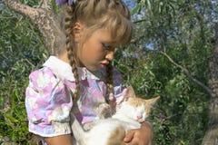 Kleines qirl mit ihrer roten Katze Lizenzfreie Stockbilder