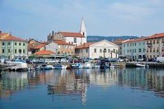 Kleines Quadrat mit Kirche und Autos am Hafen von Izola lizenzfreie stockfotografie