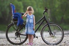 Kleines recht blondes Mädchen im blauen Kleid, das die oben stehenden Daumen herstellt Stockbild