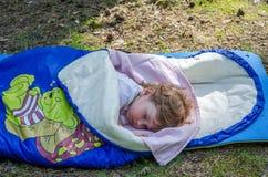 Kleines reizend Mädchenbaby, schlafend in einem Schlafsack nahe aus den Grund, mit narisovanna Schlafenbären im Wald kampieren Stockbilder