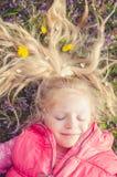 Kleines reizendes Kind, das in der Wiese liegt Stockbilder