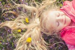 Kleines reizendes Kind mit Blumen im Haar Lizenzfreie Stockfotos