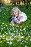 Kleines reizendes Mädchen, das im grünen Gras liegt Stockfotos