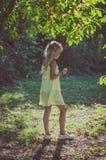 Kleines reizendes Mädchen im gelben Kleid, das unter dem Baum steht Lizenzfreies Stockfoto