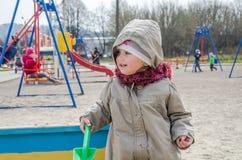 Kleines reizendes Mädchenbaby, das im Sandkasten auf dem Spielplatz mit einer Schaufel und einem Eimer gräbt ein Loch, gekleidet  Stockbild