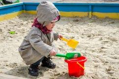 Kleines reizendes Mädchenbaby, das im Sandkasten auf dem Spielplatz mit einer Schaufel und einem Eimer gräbt ein Loch, gekleidet  Lizenzfreie Stockfotografie