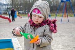 Kleines reizendes Mädchenbaby, das im Sandkasten auf dem Spielplatz mit einer Schaufel und einem Eimer gräbt ein Loch, gekleidet  Lizenzfreies Stockfoto