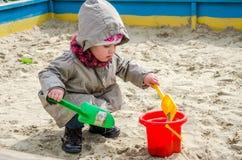 Kleines reizendes Mädchenbaby, das im Sandkasten auf dem Spielplatz mit einer Schaufel und einem Eimer gräbt ein Loch, gekleidet  Stockfotografie