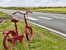 Rotes Fahrrad auf dem Straßenrand Stockbild