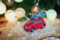 Kleines rotes Auto vor einer Weihnachtsniederlassung verziert mit illu Stockbild