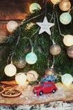 Kleines rotes Auto vor einer Weihnachtsniederlassung verziert mit illu Lizenzfreies Stockfoto