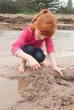 Kleines rotes behaartes Mädchen, das ein Sandburg mit nassem Sand an a errichtet Stockfoto