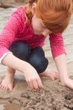 Kleines rotes behaartes Mädchen, das ein Sandburg mit nassem Sand an a errichtet Lizenzfreie Stockbilder