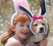 Kleines rotes behaartes Mädchen mit Schoßhund kleidete oben in den Osterhasenohren an Lizenzfreie Stockbilder