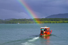 Kleines rotes Boot auf dem Fluss mit Regenbogen Lizenzfreies Stockfoto