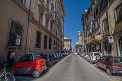 Kleines rotes Elektroauto auf Straße Borgo Ognissanti in Florenz Lizenzfreie Stockfotografie