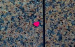 Kleines rotes Herz auf der Steinoberfläche Lizenzfreies Stockbild