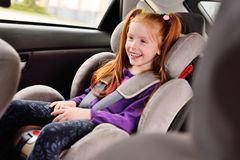 Kleines rothaariges lächelndes Mädchen des Babys beim Sitzen in einem Kinderautositz lizenzfreies stockfoto