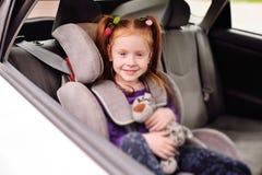 Kleines rothaariges lächelndes Mädchen des Babys beim Sitzen in einem Kinderautositz lizenzfreie stockbilder