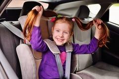 Kleines rothaariges lächelndes Mädchen des Babys beim Sitzen in einem Kinderautositz lizenzfreie stockfotos