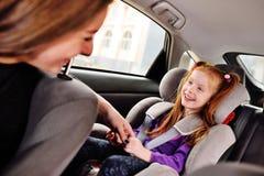Kleines rothaariges lächelndes Mädchen des Babys beim Sitzen in einem Kinderautositz stockbild