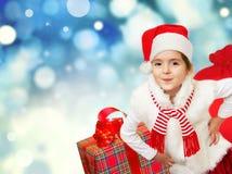 Kleines Sankt-Mädchen mit Geschenken Abstraktes Hintergrundmuster der weißen Sterne auf dunkelroter Auslegung Stockbild