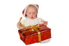Kleines Schätzchen, das ein Weihnachtsgeschenk löst lizenzfreie stockfotografie
