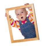 Kleines Schätzchen, das einen Bilderrahmen anhält Lizenzfreie Stockfotos