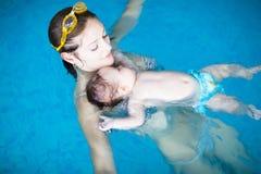 Kleines Schätzchen mit blauen Augen lernend zu schwimmen Lizenzfreie Stockfotografie