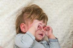 Kleines schönes Baby, das auf dem Bett liegt, Tränen von ihren Augenhänden schreit und abwischt Stockfoto