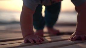 Kleines schönes Baby, das auf einen hölzernen Ruhesessel nahe dem Meer während des Sonnenuntergangs kriecht stock video footage